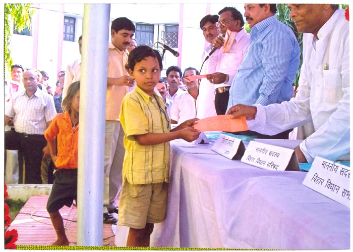 Cash is being given to a mahadalit child in Saharsa District